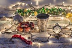 Orologio da tasca con le date, il rosario e la tazza dell'acqua con scrittura di Allah in arabo immagini stock