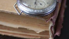 Orologio da tasca d'annata accanto al vecchio libro sbiadito, video d archivio