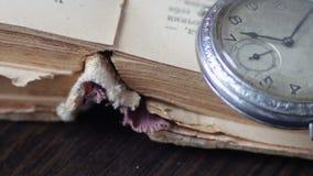 Orologio da tasca d'annata accanto al vecchio libro sbiadito, archivi video