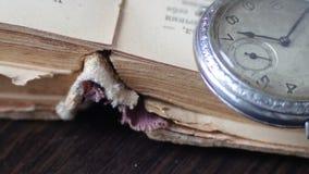 Orologio da tasca d'annata accanto al vecchio libro sbiadito, stock footage