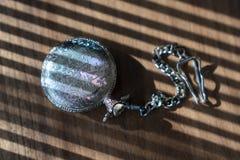 Orologio da tasca d'annata con ombra su fondo di legno nell'ambito del fascio luminoso immagine stock