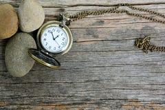 Orologio da tasca d'annata e pietra su di legno Fotografia Stock