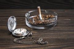 Orologio da tasca d'annata e sigaretta sgualcita in portacenere di vetro immagine stock
