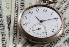 Orologio da tasca d'annata sulle banconote del dollaro Immagini Stock