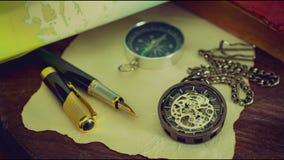 Orologio da tasca di lasso di tempo con i vecchi libri e penna con la mappa della carta archivi video