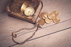 Orologio da tasca e libro dorati su legge Immagini Stock