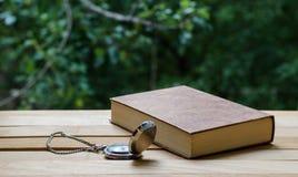 Orologio da tasca ed il libro fotografia stock