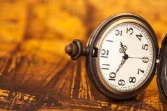 Orologio da tasca sul vecchio fondo della mappa, Immagine Stock