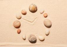 Orologio dalle pietre del mare sulla sabbia Priorità bassa della spiaggia di estate Fotografie Stock