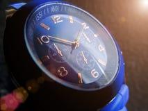 Orologio del primo piano blu di colore su un fondo grigio immagini stock