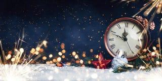Orologio del ` s dell'nuovo anno Decorato con le palle, la stella e l'albero su neve fotografie stock libere da diritti