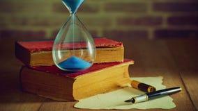 Orologio della sabbia di lasso di tempo con i vecchi libri e penna con vecchia carta sulla tavola di legno archivi video