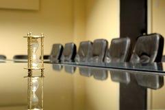 Orologio della sabbia nella sala per conferenze vuota Fotografie Stock