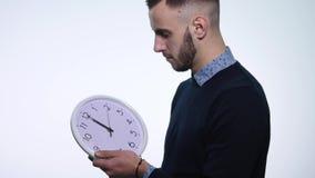 Orologio della tenuta dell'uomo su fondo bianco isolato archivi video