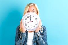 Orologio della tenuta della donna che mostra quasi 12 Immagini Stock Libere da Diritti