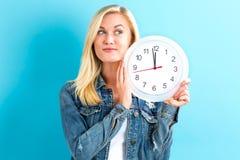 Orologio della tenuta della donna che mostra quasi 12 Fotografie Stock Libere da Diritti