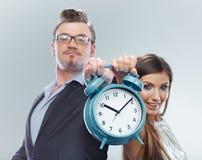 Orologio della tenuta della donna di affari e dell'uomo di affari Fotografia Stock