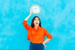 Orologio della tenuta della donna che controlla tempo su fondo blu immagine stock libera da diritti