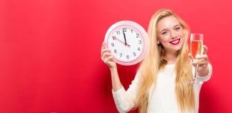Orologio della tenuta della donna che mostra quasi 12 Immagine Stock