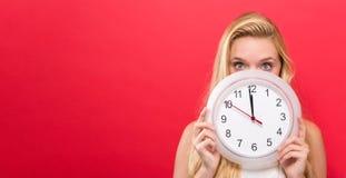 Orologio della tenuta della donna che mostra quasi 12 Fotografia Stock Libera da Diritti