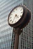 Orologio della via davanti ad un grattacielo di vetro Immagini Stock Libere da Diritti