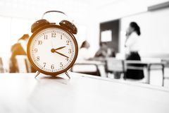 Orologio di Alam situato sulla tavola di legno dell'insegnante nella stanza dell'esame finale della s Immagine Stock Libera da Diritti