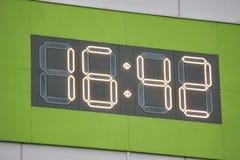 Orologio di Digital sulla parete Fondo verde città fotografie stock