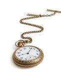 Orologio di oro d'annata con la catena che si trova sul fondo bianco Immagine Stock