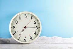 Orologio di parete bianco d'annata sulla tavola di legno fotografia stock libera da diritti