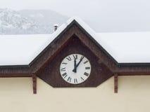 Orologio di parete con i numeri romani che segnano cinque minuti dopo mezzogiorno Fotografia Stock