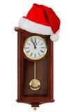 Orologio di parete e cappuccio di Santa Claus, isolati su fondo bianco Fotografie Stock