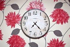 Orologio di parete isolato sulla carta da parati sopra colorata Immagini Stock