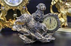 Orologio di tavola bronzeo con i cani su una tavola di legno immagini stock libere da diritti