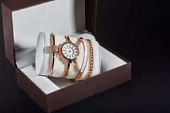 Orologio dorato della donna su un fondo bianco nella scatola Fotografie Stock