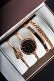 Orologio dorato della donna su un fondo bianco nella scatola Immagine Stock