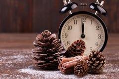 Orologio e coni del nuovo anno coperti di neve Fotografia Stock