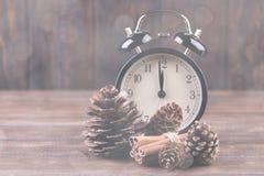 Orologio e coni del nuovo anno coperti di neve Immagini Stock