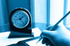 Orologio e mano di scrittura sulla nota Fotografia Stock Libera da Diritti