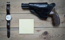 Orologio e taccuino del revolver Immagine Stock