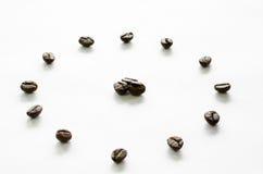 Orologio fatto dai chicchi di caffè su fondo bianco, caffè di amore immagine stock