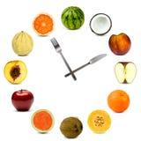 Orologio fatto dell'insieme differente della composizione nella frutta isolato su bianco Fotografie Stock