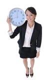 Orologio felice della holding della donna di affari Immagini Stock