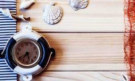 Orologio marino decorativo sui precedenti dei bordi di legno Fotografia Stock