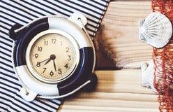 Orologio marino decorativo sui precedenti dei bordi di legno Fotografie Stock