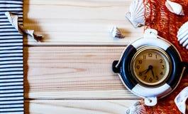 Orologio marino decorativo sui precedenti dei bordi di legno Immagine Stock