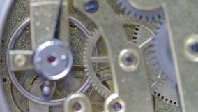 Orologio meccanico d'ottone corrente con il fuoco sugli ingranaggi su fondo stock footage
