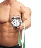 Orologio muscolare della tenuta dell'uomo e nastro di misurazione Fotografia Stock Libera da Diritti