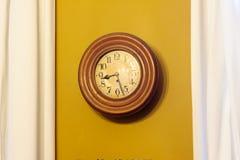 Orologio ocraceo contro la parete fotografie stock libere da diritti
