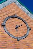 Orologio rotondo stilizzato sul muro di mattoni del façade della costruzione con il coni Fotografia Stock