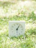 Orologio semplice bianco sull'iarda del prato inglese, 1:05 uno cinque Immagine Stock